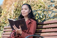 Pleased brunette female person being deep in thoughts. Keep calm. Kind girl keeping smile on face while thinking about Holy Bible stock images