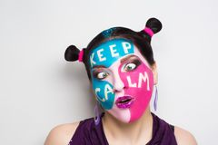 Keep calm make up. Young beautiful woman girl lady with Keep calm inscription picture words on her face. model fashionable beam hairdo, professional makeup royalty free stock photos