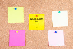 Keep calm and... on a sticky note on cork board Royalty Free Stock Images