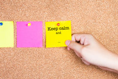 Keep calm and... on a sticky note on cork board with hand holding Royalty Free Stock Photography