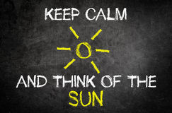 Keep Calm and Think of the Sun Concept on a Board Stock Photo