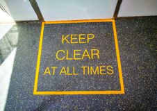 Keep clear at all times sign on the train floor. Caution sign which indicates a potential hazard, obstacle or condition requiring special attention Keep clear stock photography
