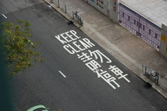 Keep clear in English and Chinese painted on the street Stock Image