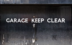 Keep clear!. Garage keep clear sign on black doors Royalty Free Stock Photos