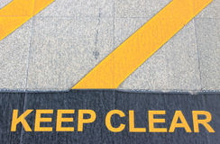 Keep clear sign. Keep clear written on electric train station floor Stock Image