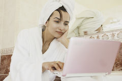 Keep It Close By. Young woman using computer while in bathroom Stock Photography