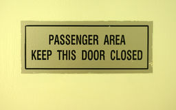 Keep this door closed sign. Passenger area keep this area closed sign on ship stock image