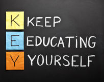Keep-educating-yourself-acronym. KEY acronym - KEEP EDUCATING YOURSELF. Educational concept with different color sticky notes and white chalk handwriting on a Royalty Free Stock Photo