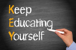 Keep Educating Yourself Words on Blackboard. KEY - Keep Educating Yourself. Education concept on chalkboard or blackboard with female hand and chalk Stock Photo