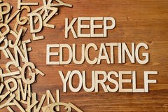 Keep Educating Yourself. Words made with wooden letters on the plank table Royalty Free Stock Images