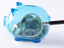 Keep an eye on your savings. Magnified coins in a piggy bank. Studio shot Stock Images