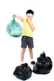 Keep garbage in bag for eliminate. Young Asian boy carry garbage in plastic bag that bad smell for eliminate on the white background stock image
