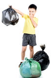 Keep garbage in bag for eliminate. Young Asian boy carry garbage in plastic bag that bad smell for eliminate on the white background royalty free stock photography