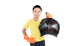 Keep garbage in bag for eliminate. Young Asian boy in orange gloves carry garbage in plastic bag for eliminate on the white background Stock Photos