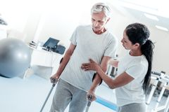 Determined woman helping old man stand. Keep going. Attractive concentrated dark-haired women helping a serious old grey-haired men stand and holding him while Stock Photos