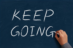Keep Going. On blue chalkboard with the hand of businessman Royalty Free Stock Image