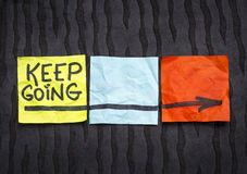Keep going motivation concept. Keep going - motivation or determination concept - handwriting on colorful sticky notes against black lokta paper Stock Images