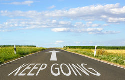 Keep Going - street with arrow and text. Blue sky and clouds in the background - motivation concept Royalty Free Stock Photography