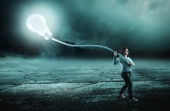 Keep on with an idea. Woman walk at night and carry a lightbulb. The concept of keep on with an idea all the way Stock Images