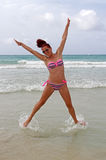 Keep on jumping. Fully fit mature woman jumping in the shallow water of the Caribbean Sea royalty free stock photo
