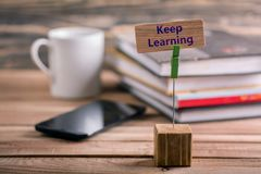 Keep learning. On wooden card with book , coffee cup and mobile phone on wooden table Stock Photos