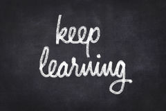 Keep learning written on chalkboard. Education - keep learning - handwritten on chalkboard background Stock Photo