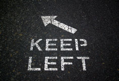 Keep Left Sign. Keep left, sign, paint, white, road, path, gravel, track, cement, bitumen, direction, arrow Royalty Free Stock Image