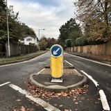 Keep Left Traffic Bollard. A Keep Left Traffic Bollard or road sign on a typical street in England during Autumn weather stock photo