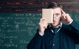 Keep in mind. Teacher formal wear and glasses looks smart, chalkboard background. Man unshaven holds book in front of royalty free stock image