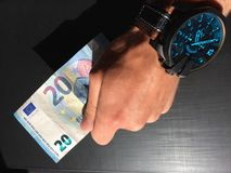 Keep money, money in the palm of your hand, receive money, give money, watch on hand, Europea. White man`s hand holds a bank note, keep money, money in the palm royalty free stock photography
