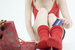 Keep the money in the sock. Young woman stuffing the credit card in her sock royalty free stock image