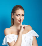 Keep my secret! Beautiful young woman holding finger on lips and looking at camera Royalty Free Stock Photos