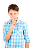 Keep my secret! Serious teen boy in plaid shirt holding finger on lips and looking at camera isolated on white background Royalty Free Stock Photos