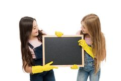 Keep it neat. School children in rubber gloves holding empty blackboard. Small pupils doing their duties during school. Time. Primary school students keeping royalty free stock photo