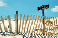 Keep off the Dunes. Beach scene with fence and sign that says keep of the dunes.  The sign is weathered.   There is a blue sky with a few clouds Stock Image