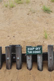 Keep off the dunes. Green keep off the dunes sign on retaining wall with sand background Royalty Free Stock Photography