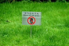 Keep off the grass 1. A lush green overgrown lawn with a sign, in english and chinese, warning to keep off the grass in a park in Hong Kong Royalty Free Stock Image