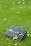 Keep off the grass. Sign on a leafy lawn Stock Image
