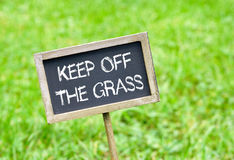 Keep off the grass - chalkboard on grass background. Keep off the grass - chalkboard on green grass background Royalty Free Stock Photography