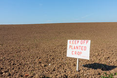 Keep off sign over looking brown field Stock Image