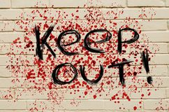 Keep Out danger inscription on a bloodstained brick wall. Royalty Free Stock Photo