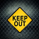 Keep Out Grunge Yellow Warning Sign on Chainlink Fence Royalty Free Stock Image