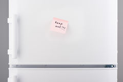 Keep out note on light pink paper on white refrigerator Royalty Free Stock Photos