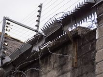 Razor wire, electric fence and metal spikes on a wall royalty free stock image