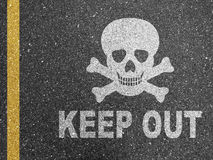 Keep out. A road with painted skull and crossbones with the text 'keep out stock photo