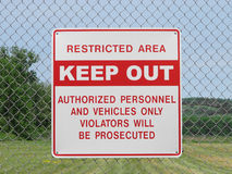 Keep out sign on a chain link fence. Red and white sign on a chain link fence with words regarding keep out and restricted area royalty free stock image