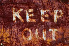Keep Out Sign. White letters sign on rusted metal plate saying Keep Out stock photo