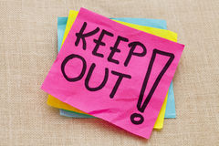 Keep out warning. Handwriting on a purple sticky note against canvas board Royalty Free Stock Image