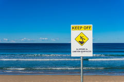 Keep out warning sign against ocean and blue sky Royalty Free Stock Image