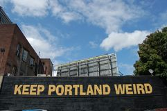Keep Portland Oregon Weird Sign. `Keep Portland Weird` is painted on the back wall of Dante`s in Portland Oregon, with a blue sky and white clouds in the royalty free stock images